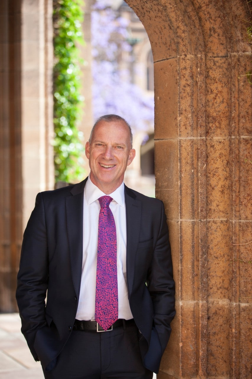 Dr Michael Spence leanign against a sandstone wall
