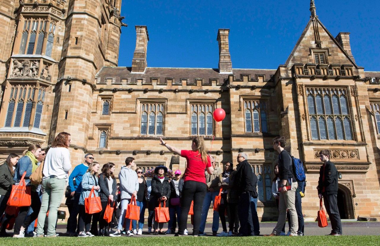 Student ambassador leading a group of visitors at Open Day on a campus tour in front of the Quadrangle