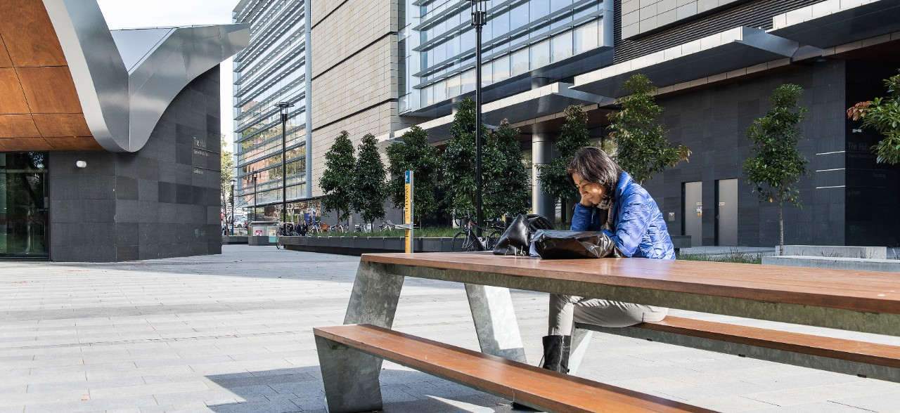 student studying at a table outside the Charles Perkins Centre
