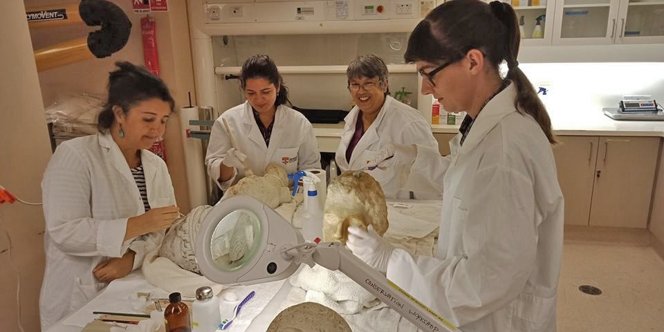 Team of conservators in white lab coats with artefacts.