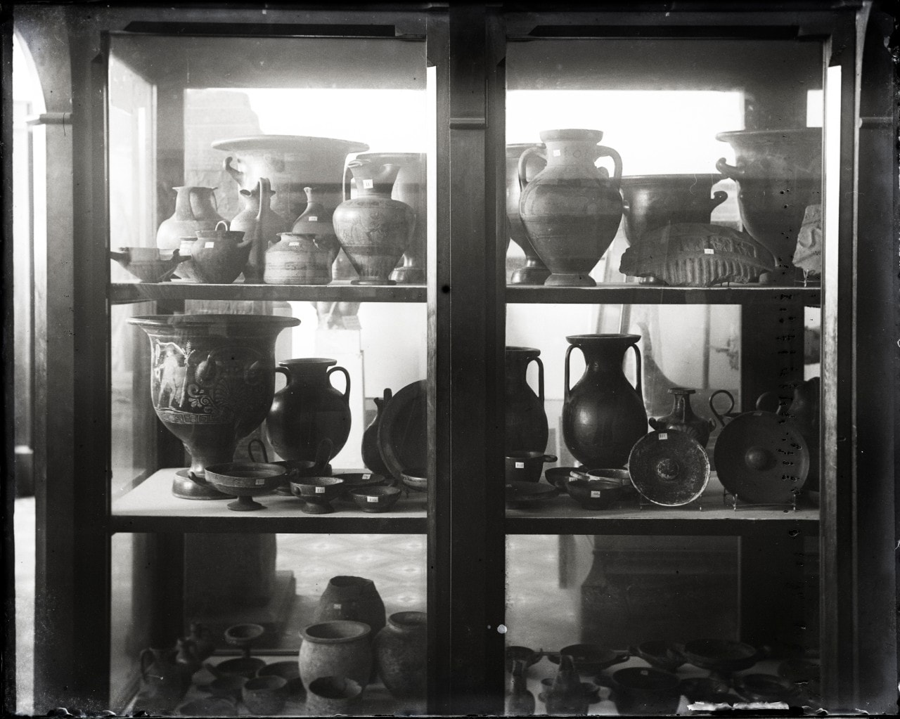 A cabinet filled with pottery.