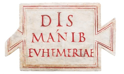 A white funeral tile with red wording etched in.