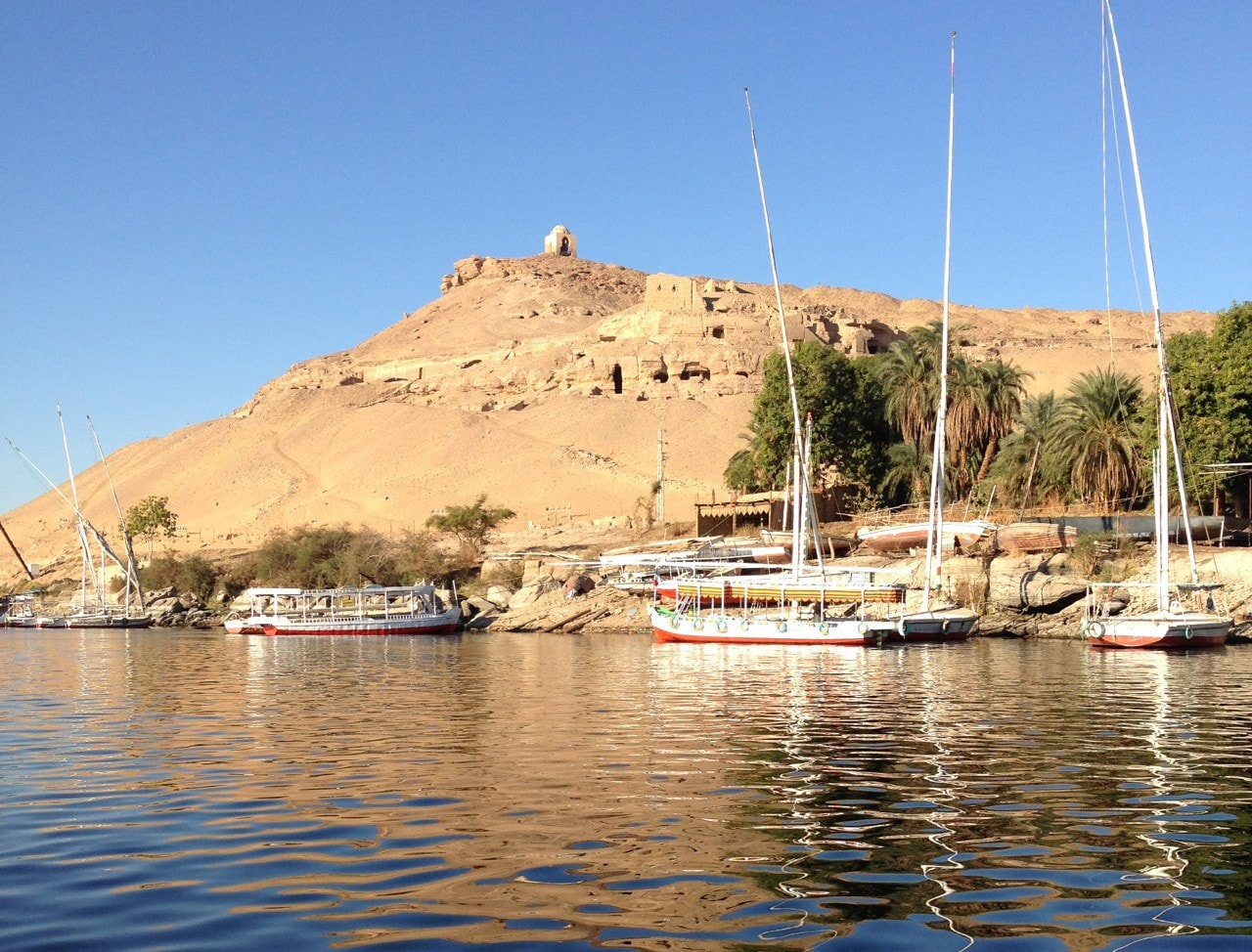 View from a boat filled harbour with a large sand covered hill in the background dotted with tombs.