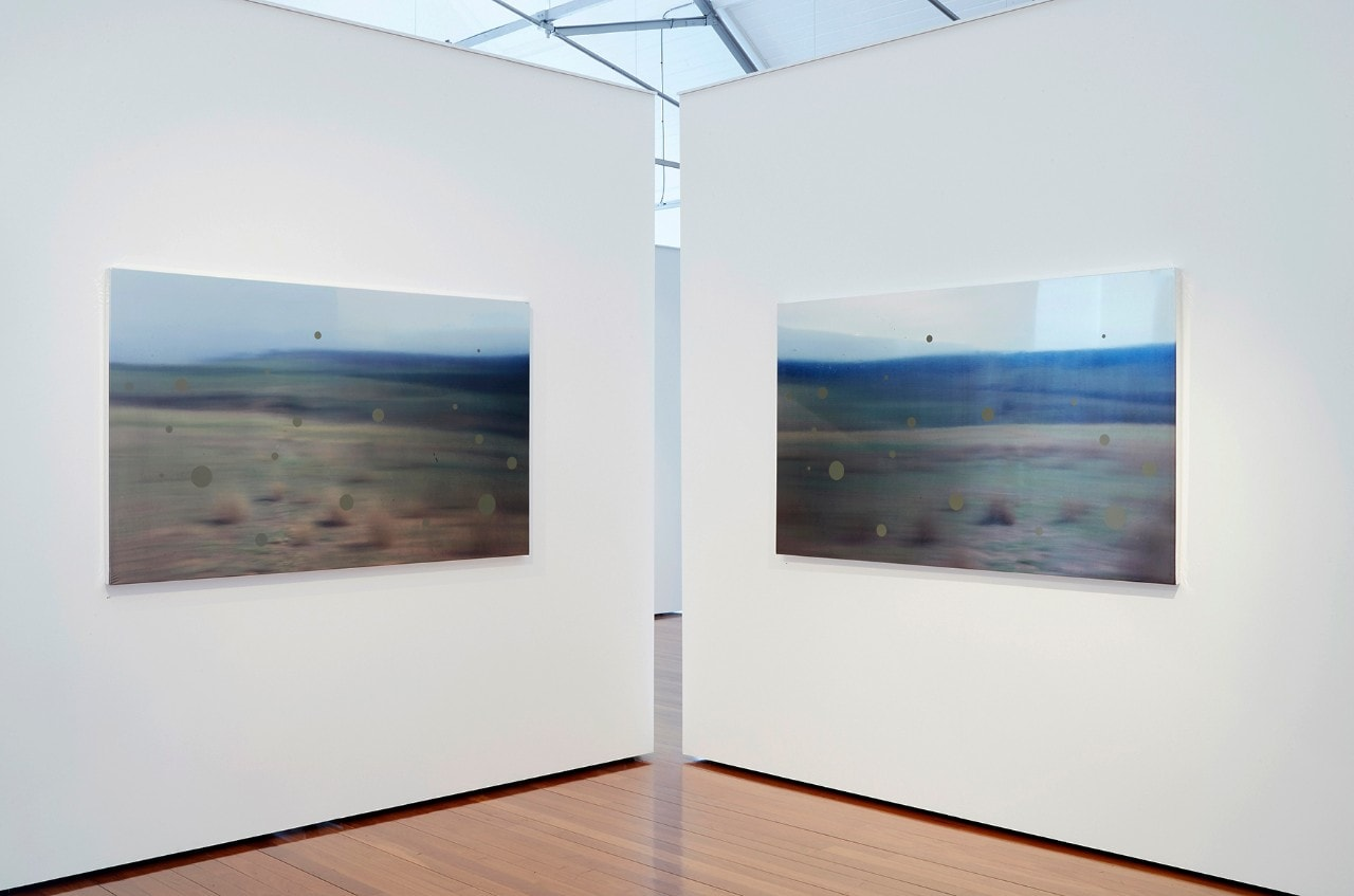 Landscape artwork on two white walls in an art gallery