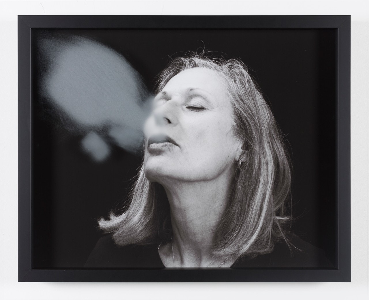 "Black and white image of woman exhaling condensate; entitled ""Blow back"" by Julie Rrap"