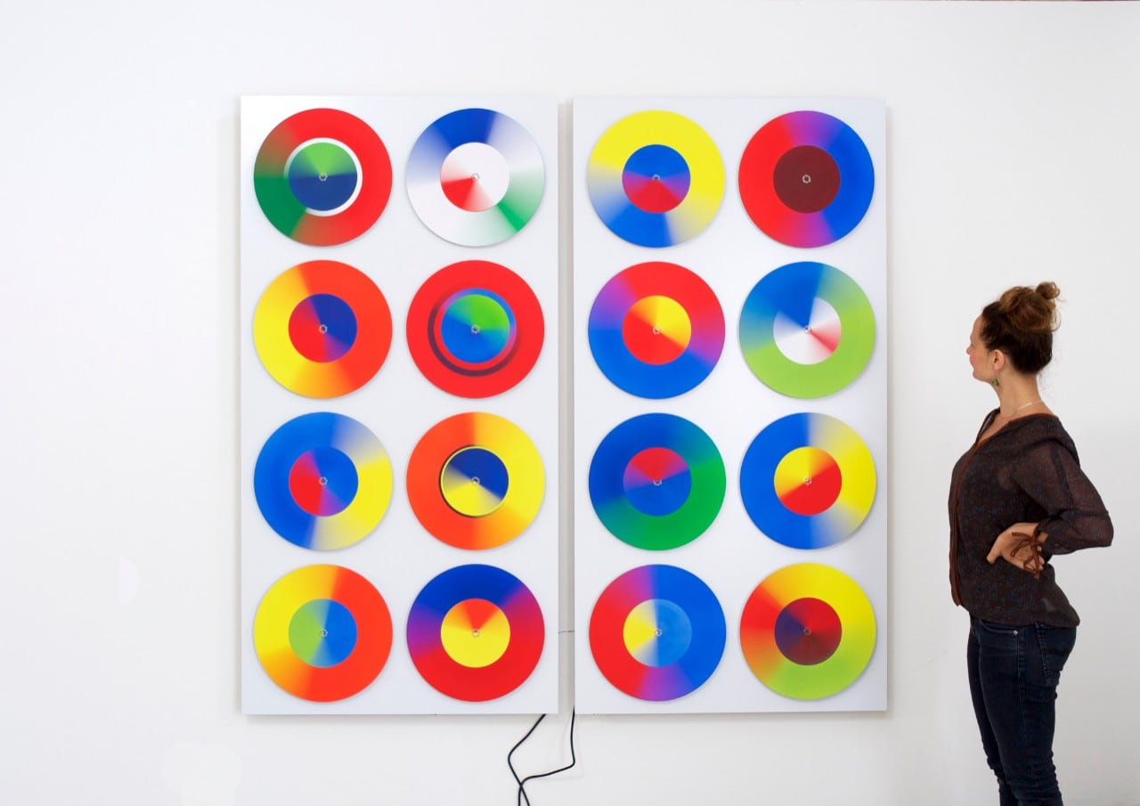 Woman looking at colourful disks on the wall