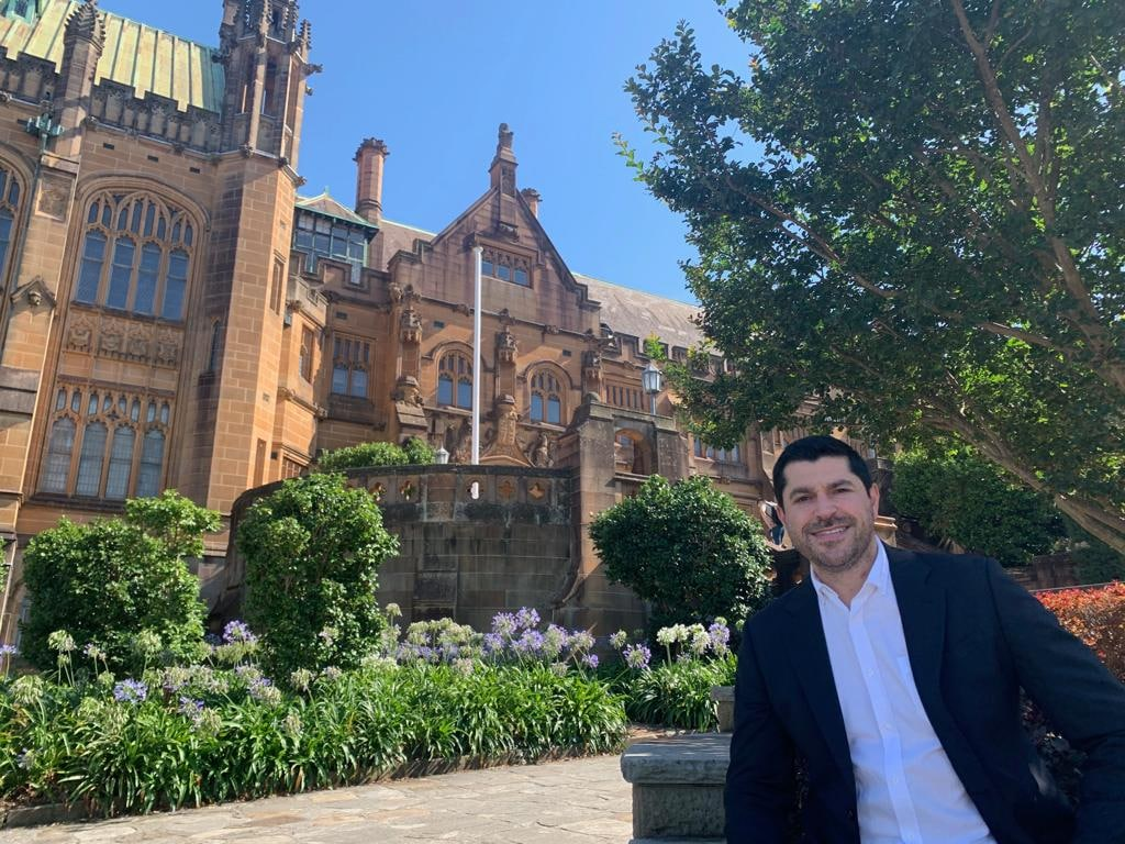 Professor PJ Cullen poses outside of a University of Sydney sandstone building