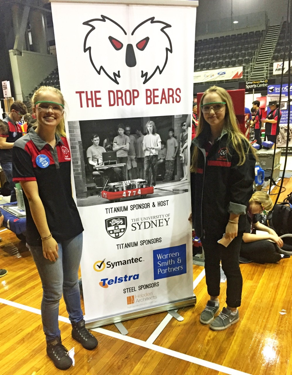 Two girls standing next to Drop Bears banner