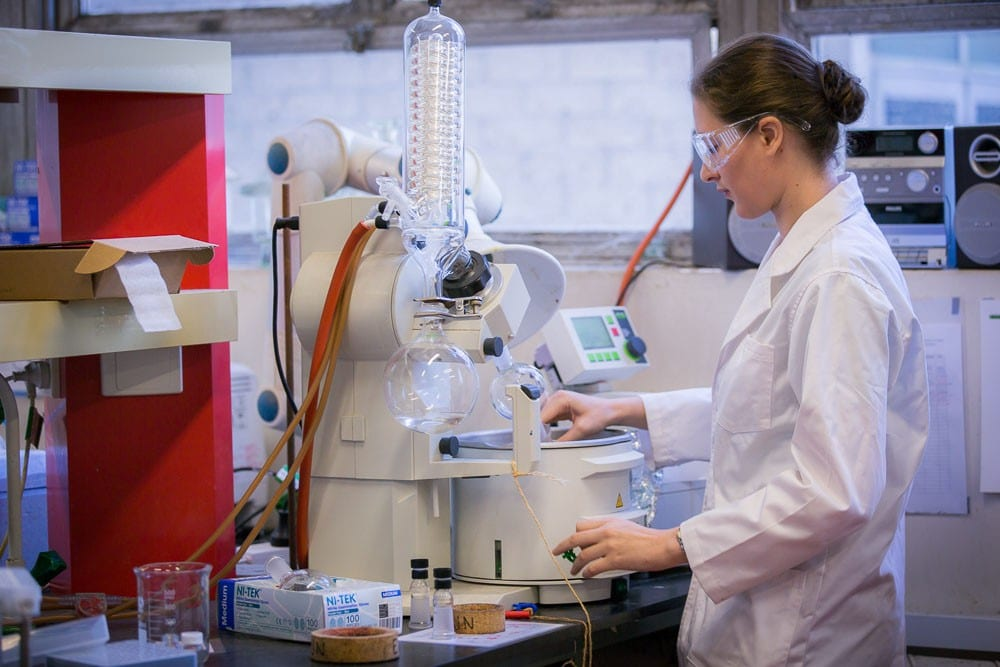 Girl in white lab coat working in lab