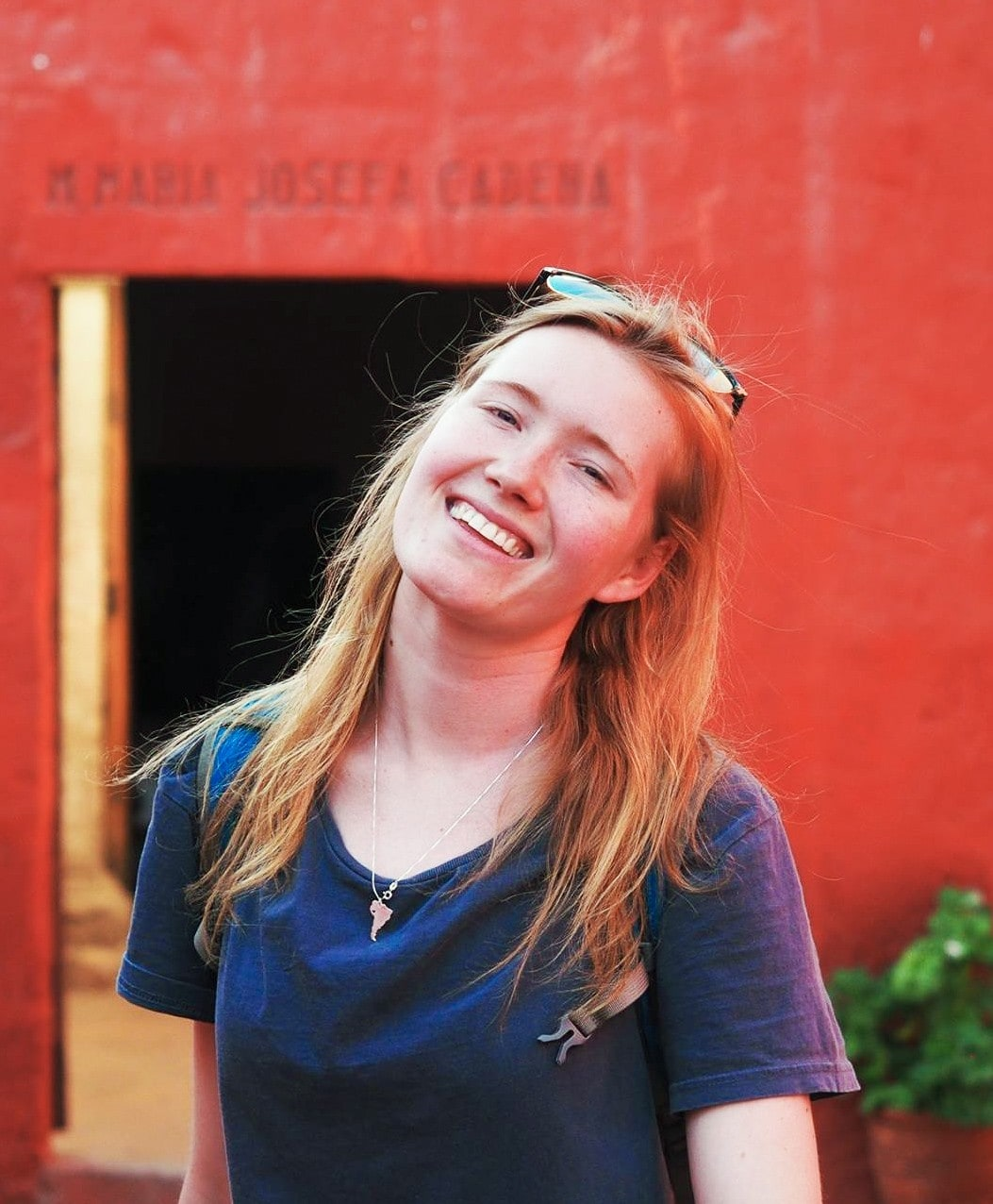 Picture of Madeleine Combe standing in front of a red wall, smiling