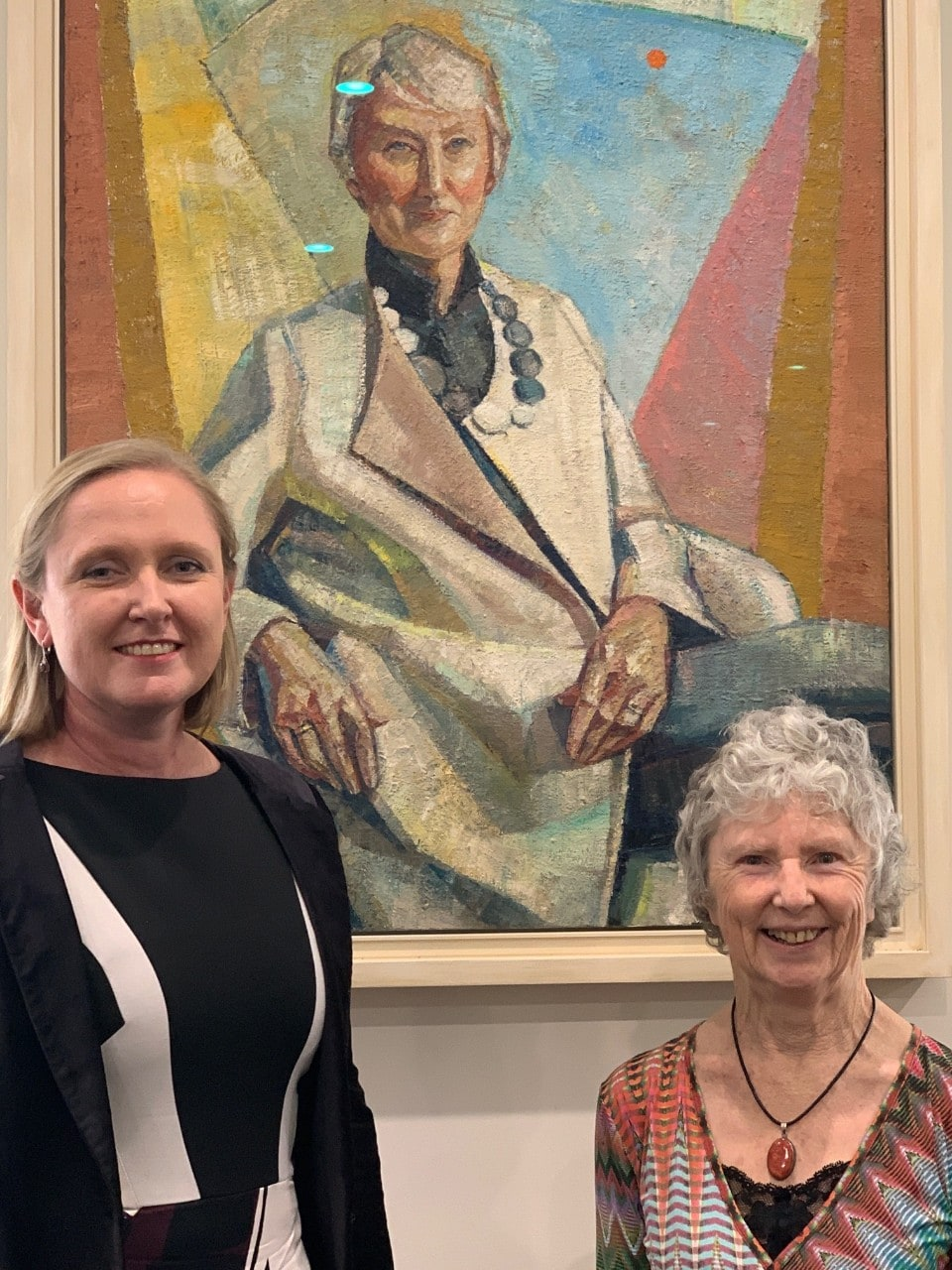 Darian McBain and Joy Murray standing in front of Yvette Coppersmith's portrait of Emeritus Professor Anne Green, President of Sydney's Physics Foundation.