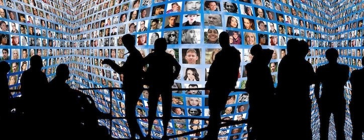 Silhouettes standing in front of a large collage of profile photos