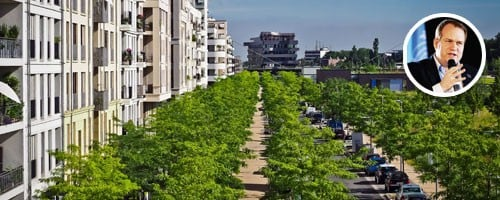 Image of a road lined with trees and apartments on the left side