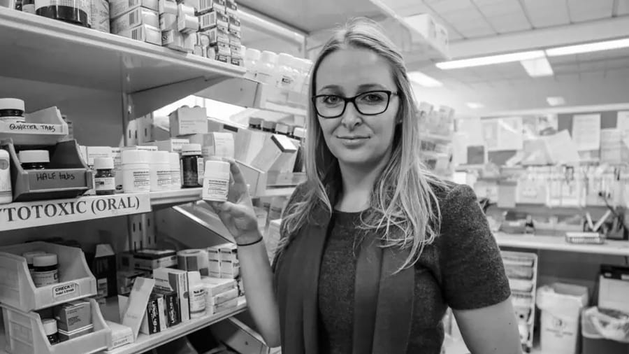 Black and white image of pharmacist Rose Cairns standing at shelves of medicines holding a small bottle