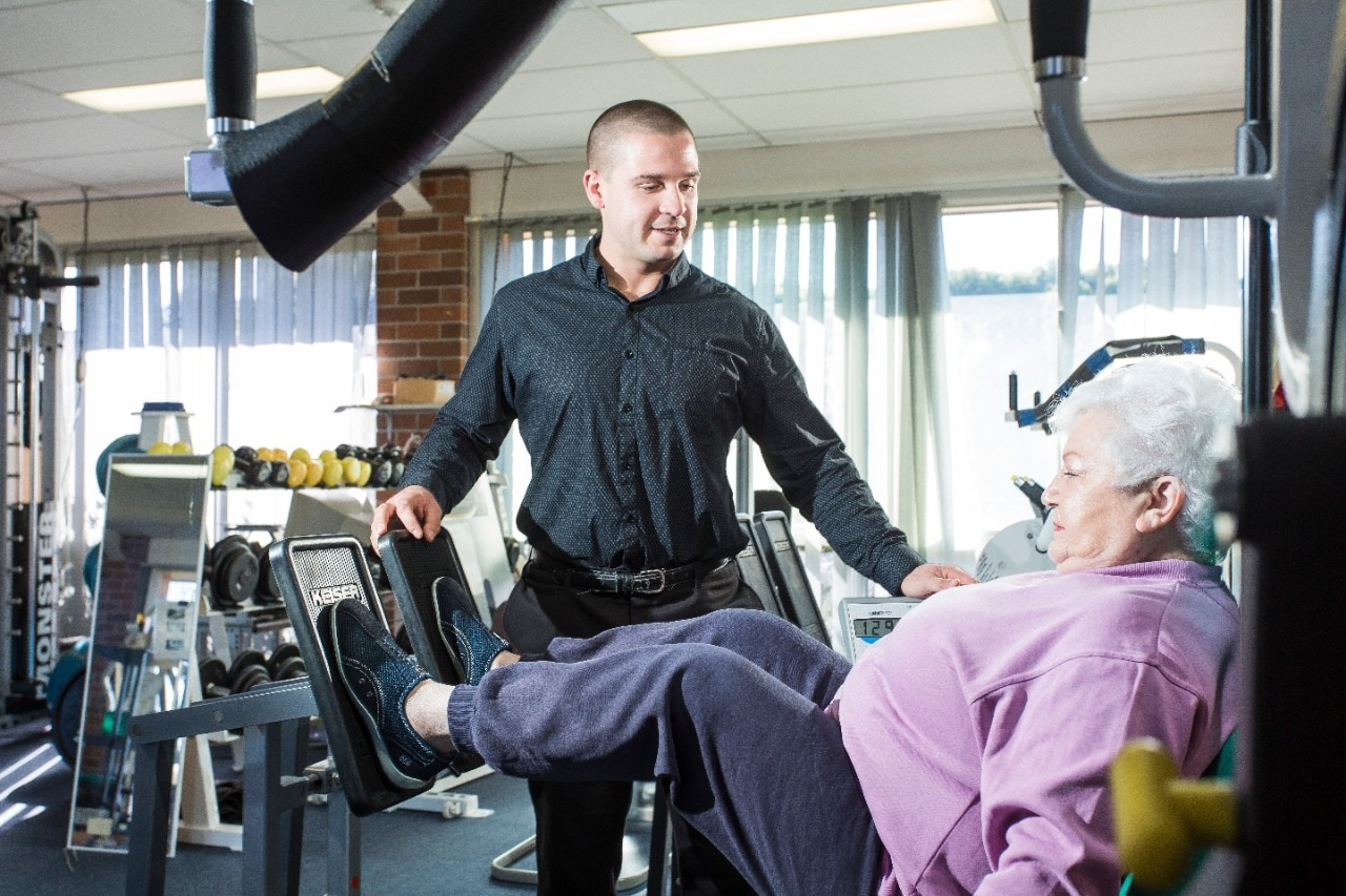 HDR student Michael Inskip instructing elderly woman doing leg presses on a weights machine in a gym