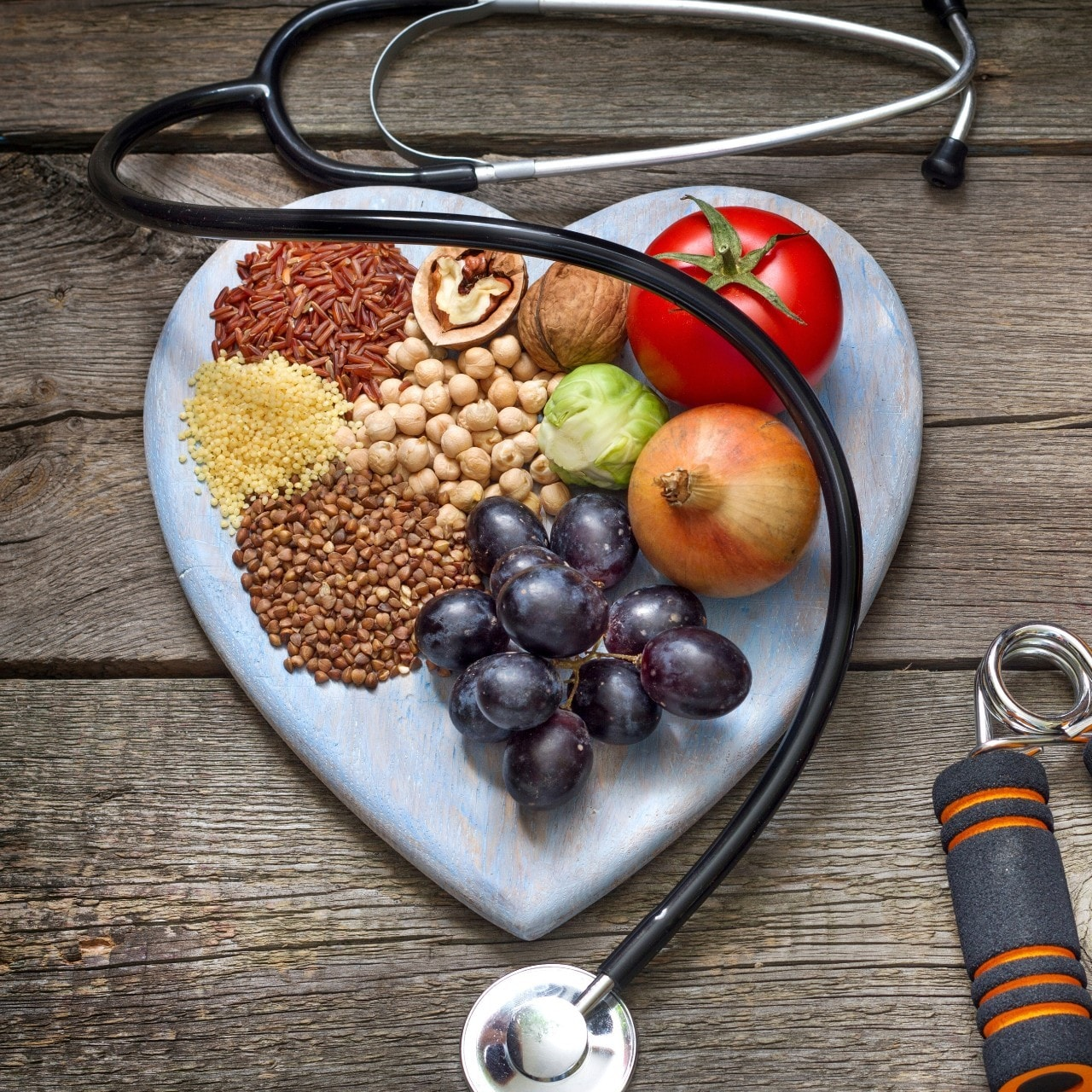 Heathly food arranged on a heart-shaped plate surrounded by a stethoscope and gym gear