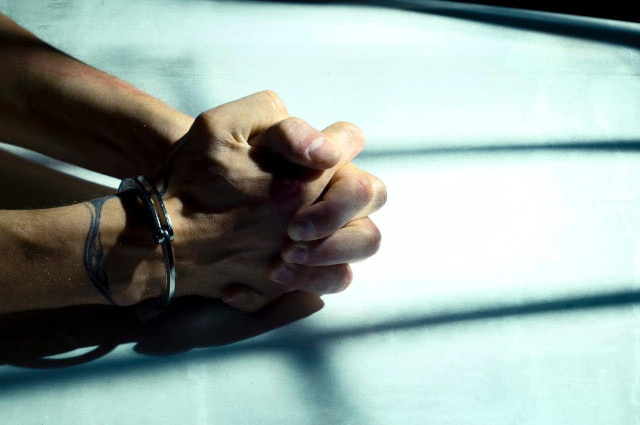 A man's hands cuffed on a table. Image: iStock