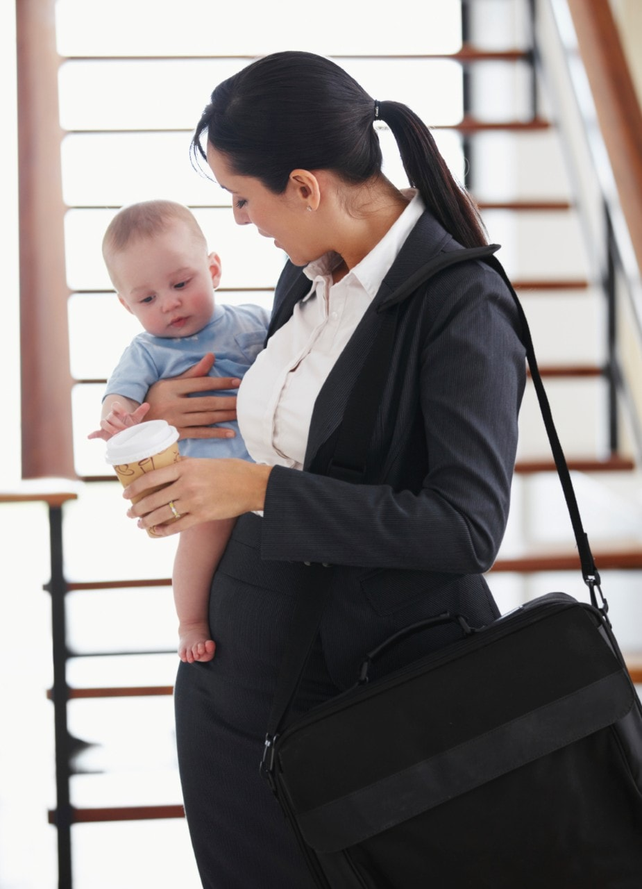 An office worker holds a child. Image: iStock