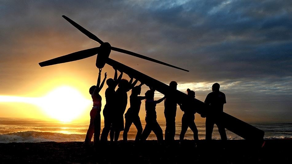 A photo of people erecting a wind turbine at sunset.