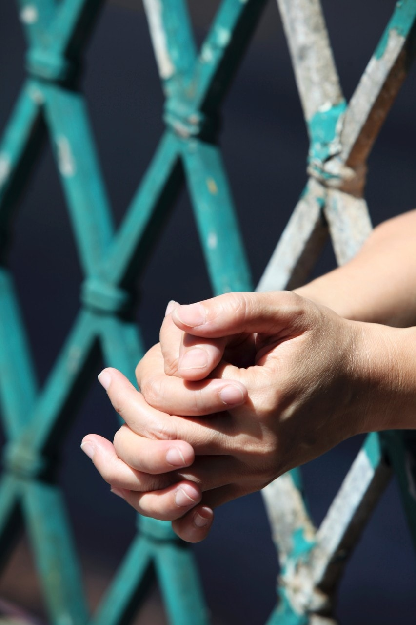 A close-up shot of clasped hands placed through prison bars. Image: iStock