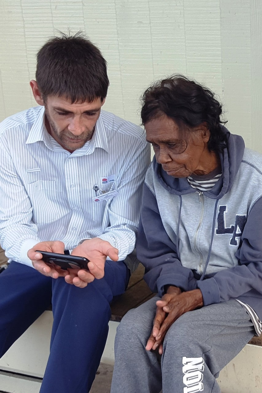 A photo of Aboriginal health workers Dan Kelly and Frances Coffey using the iECG device.
