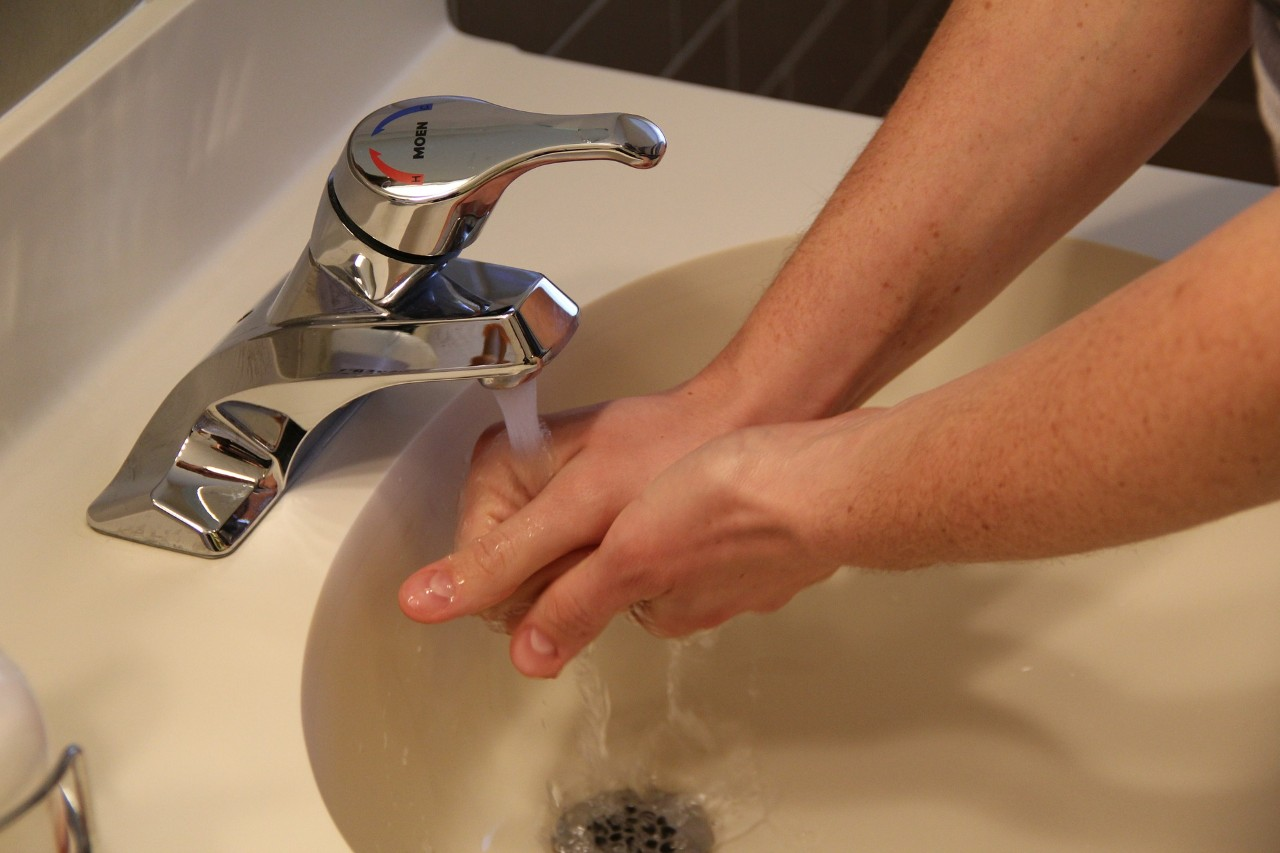 Hands being washed in a handbasin with a running tap