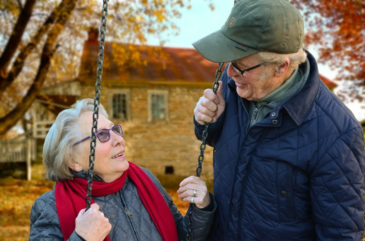 A photo of an older couple, she's on a swing.