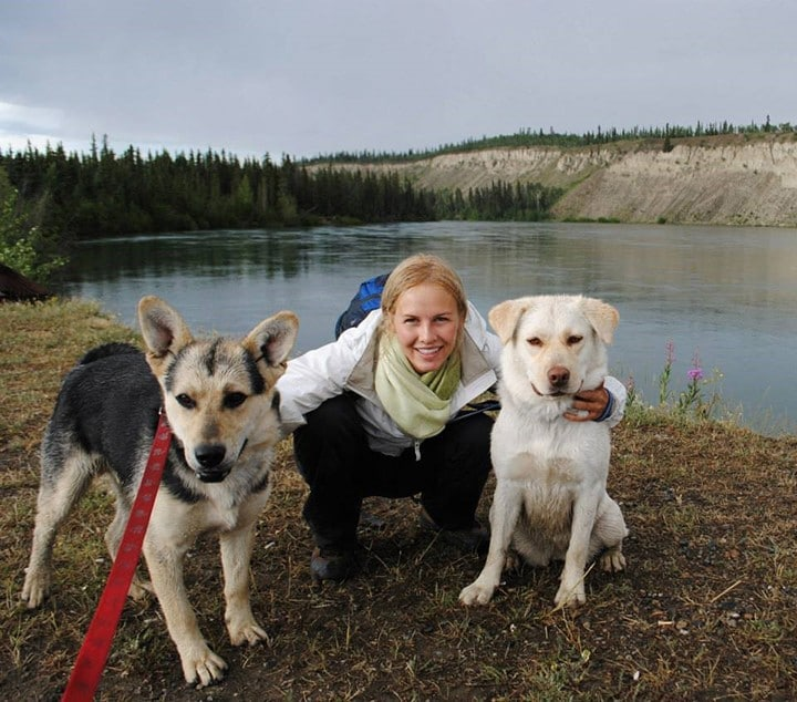 Fiona Emdin crouched in front of a lake with her two dogs.