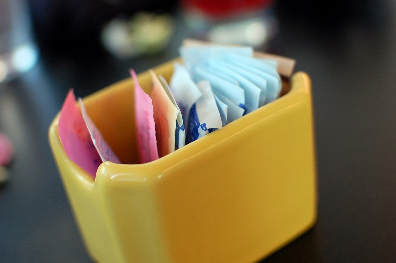 A photo of packets of artificial sweetener in a container