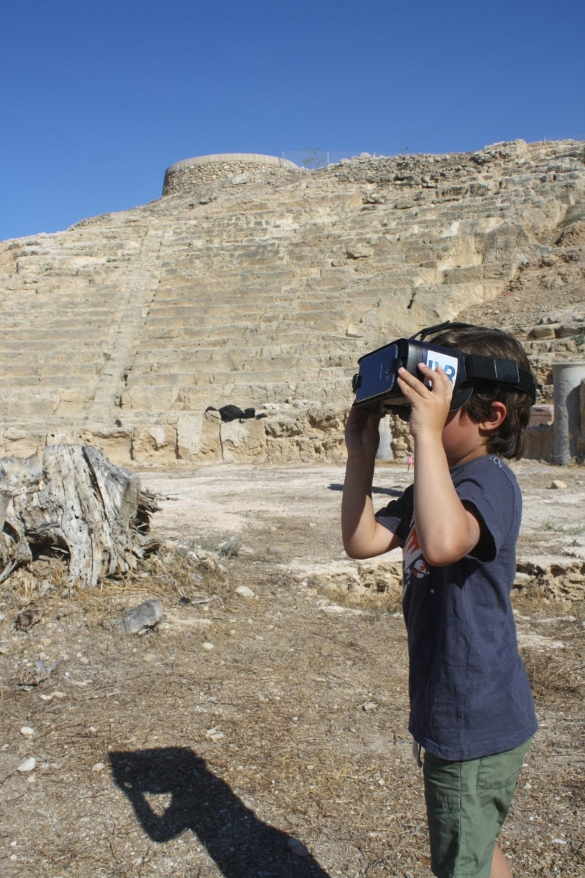 A school child on site at Nea Paphos looking at the virtual reality mobile application depicting the Nea Paphos Theatre in its heyday