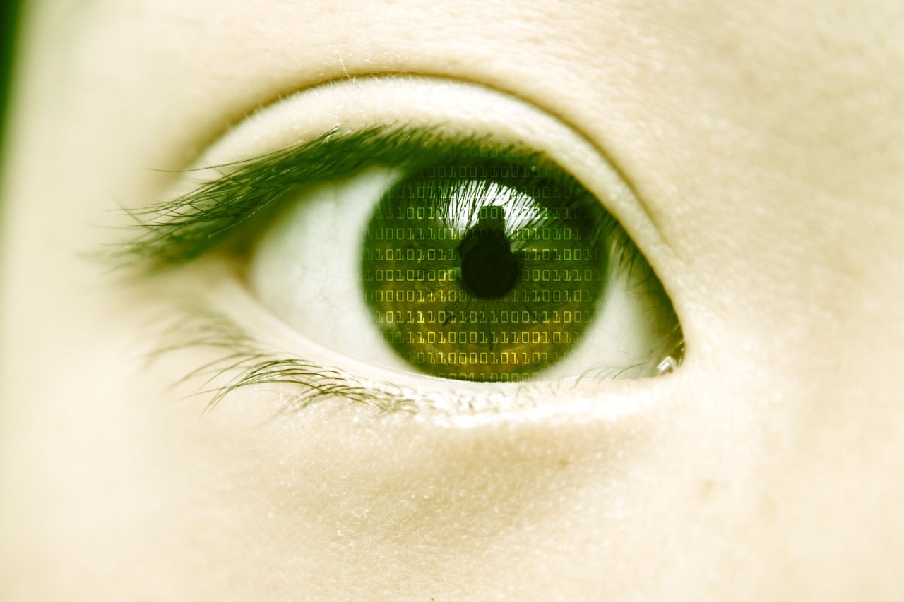 Closeup of woman's eye with binary code reflected in pupil.