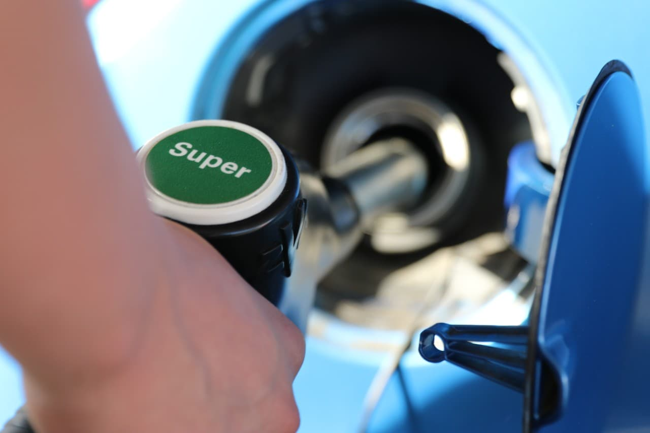 This image shows a hand holding a petrol pump refuelling a car.