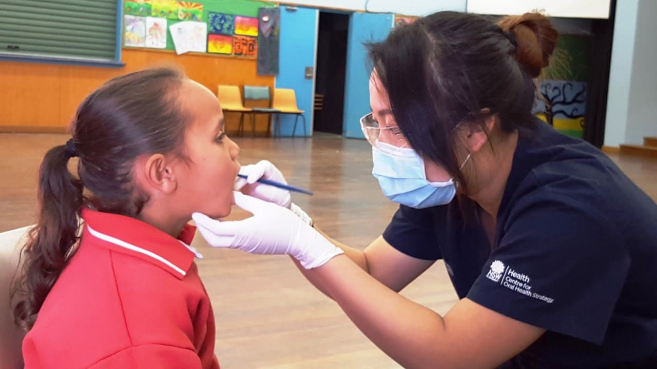 A student having their teeth checked by a health worker.