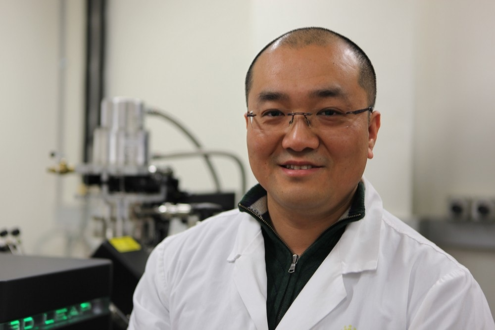 Jiangtao Qu standing in his lab.