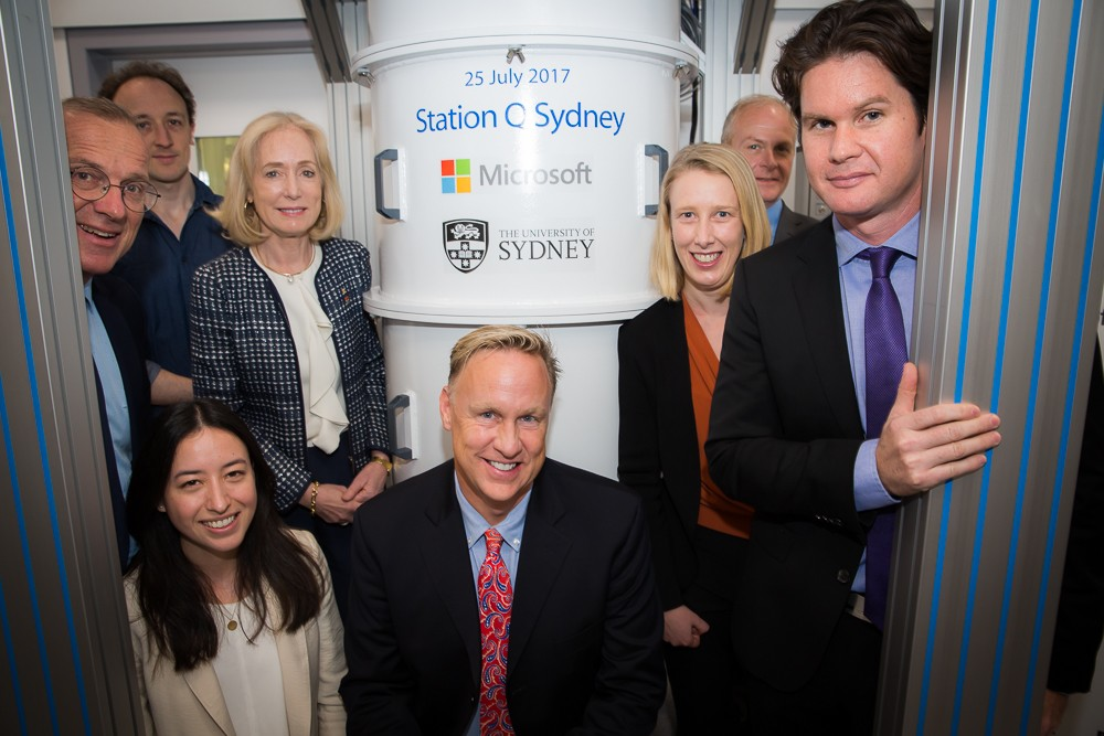 In front of one of the new specialist dilution refrigerators before the ceremonial signing.  Front row: PhD candidate Alice Mahoney with Microsoft's Chief of Staff, Artificial Intelligence and Research Group Mr David Pritchard. Back row (R-L): Station Q Sydney Scientific  director Professor David Reilly; partner architect of Microsoft's Quantum Architectures and Computation (QuArC) group Mr Douglas Carmean; Station Q Sydney senior research scientist Dr Maja Cassidy; University of Sydney Chancellor Belinda Hutchinson, Station Q Sydney postdoctoral researcher Dr John Hornibrook and University of Sydney Vice-Chancellor and Principal Dr Michael Spence. Credit: Jayne Ion.
