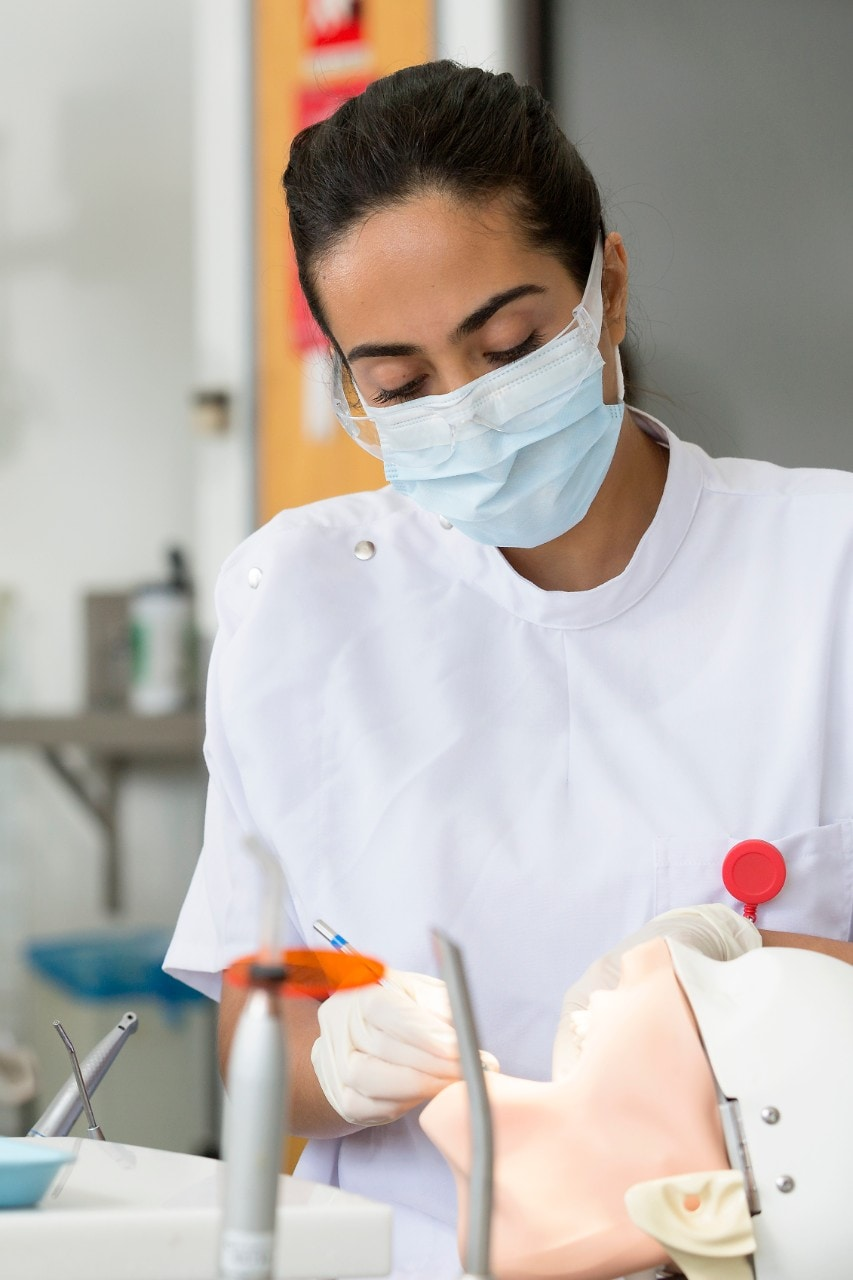 female dental student working on dummy