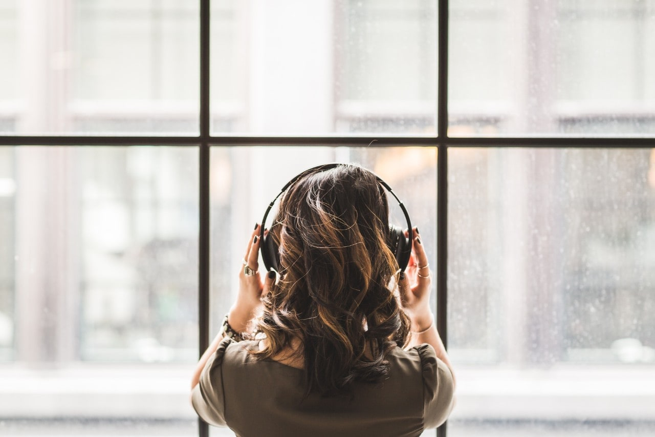 A woman with headphones on, listening to music.