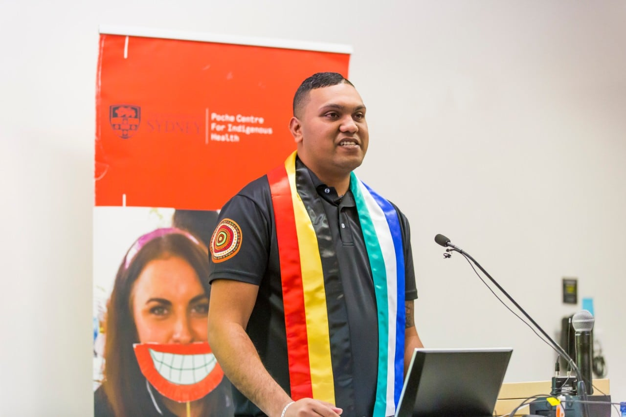 A photo of Paul Talbot, a proud Aboriginal man, speaking in front of a microphone.