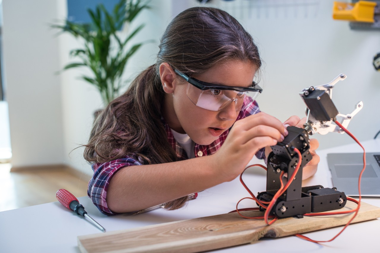 A young student repairs a robotic arm. Image: iStock