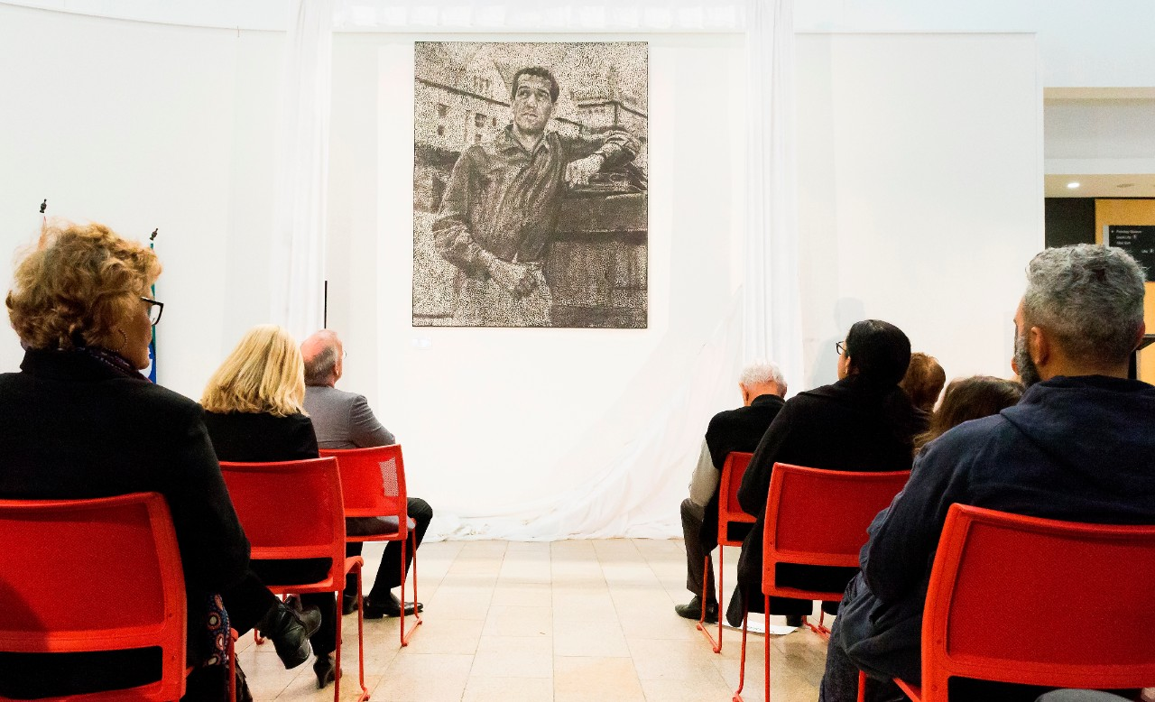 A photo of people seated, looking at a large black and white dot painting of Charles Perkins.