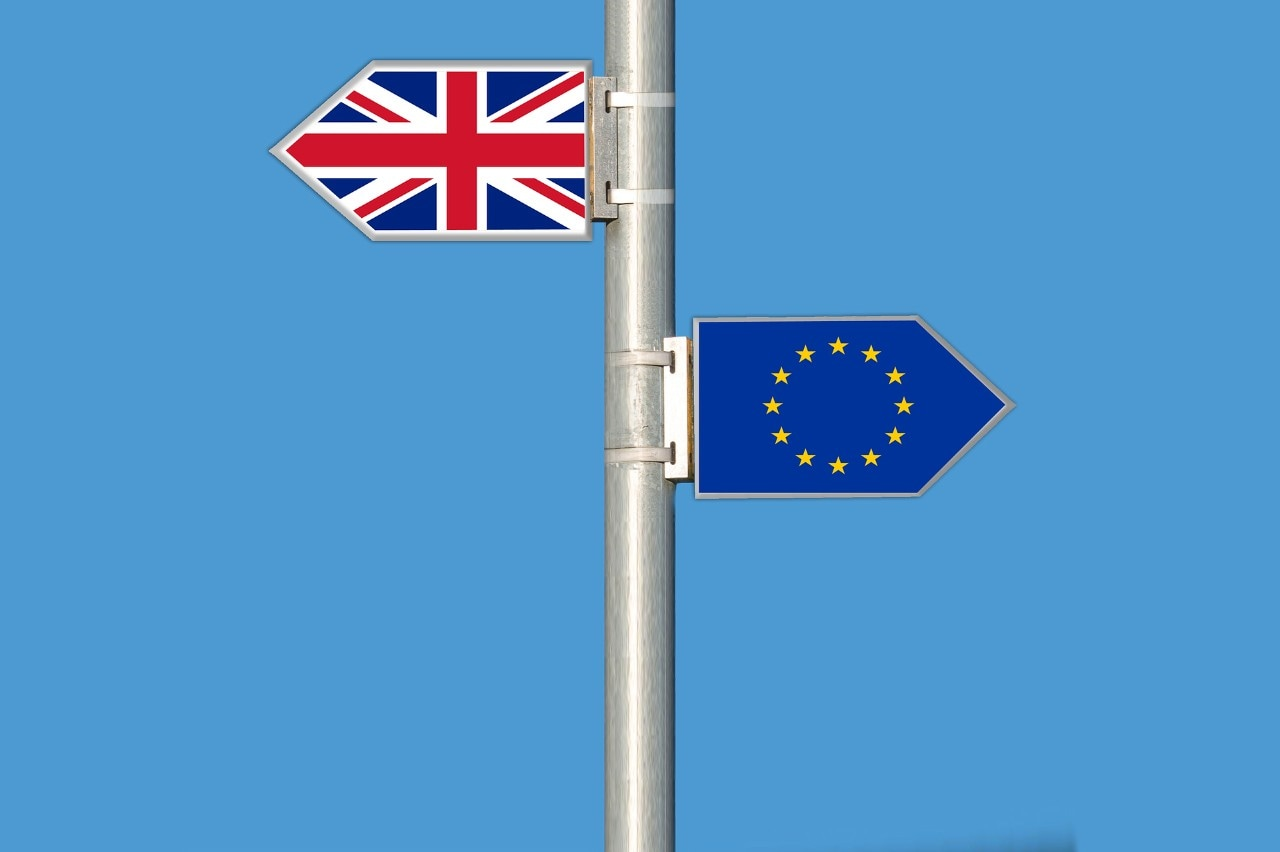 Signs of UK and EU flags pointing in opposite directions