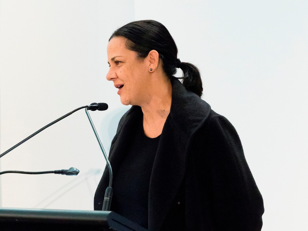 A photograph of Hetti Perkins speaking at a microphone.