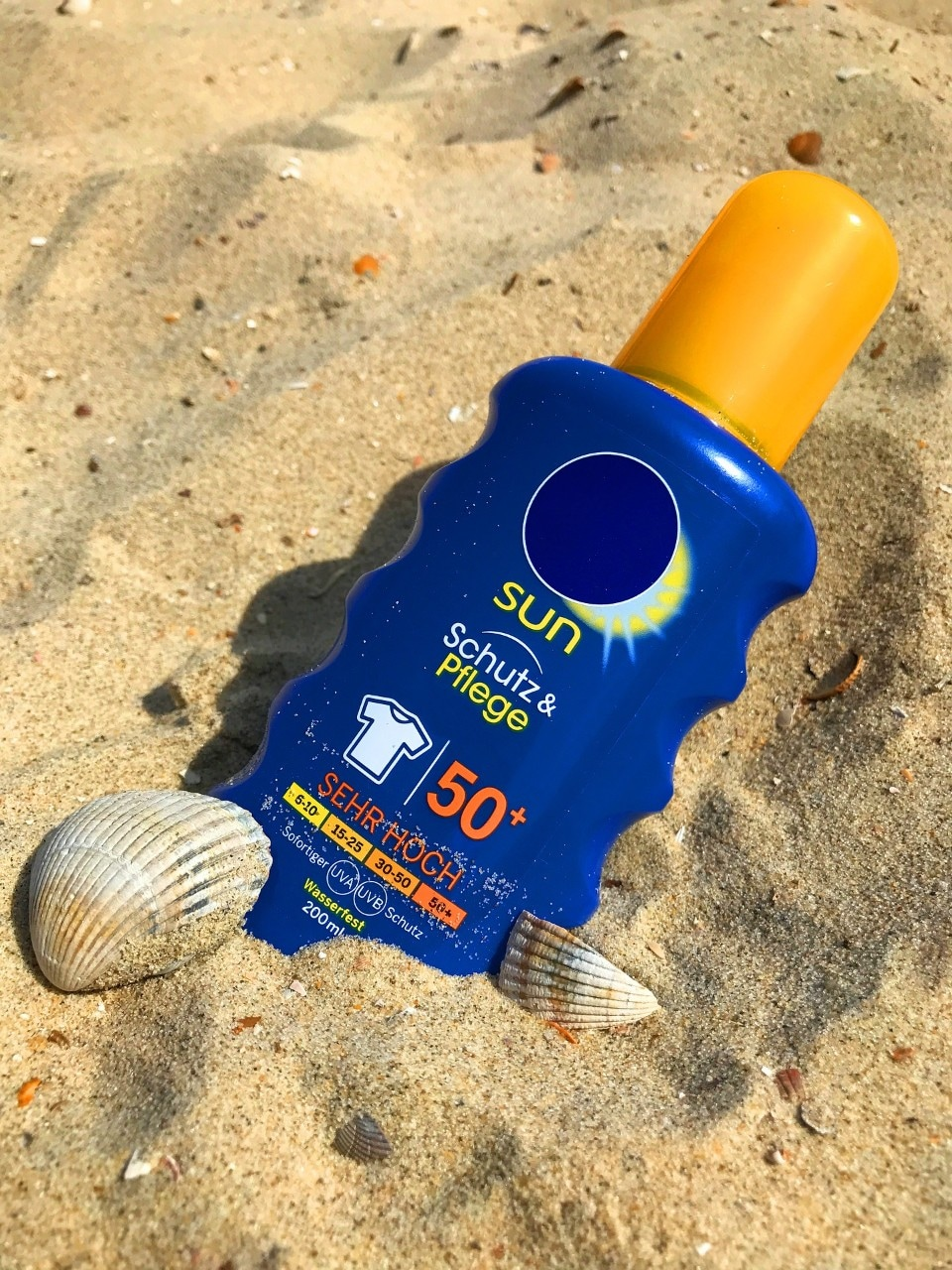 Sunblock in the sand with 'SPF 15' and 'UVA and UVB protection' on the label.
