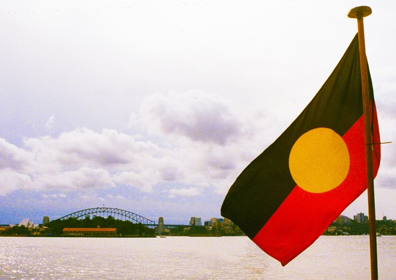A photo of an Aboriginal flag with the Harbour Bridge in the background.