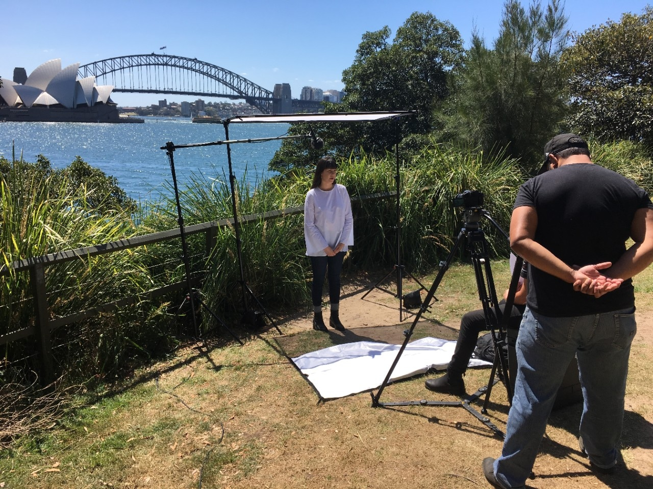 A photo of people recording video on Sydney Harbour.