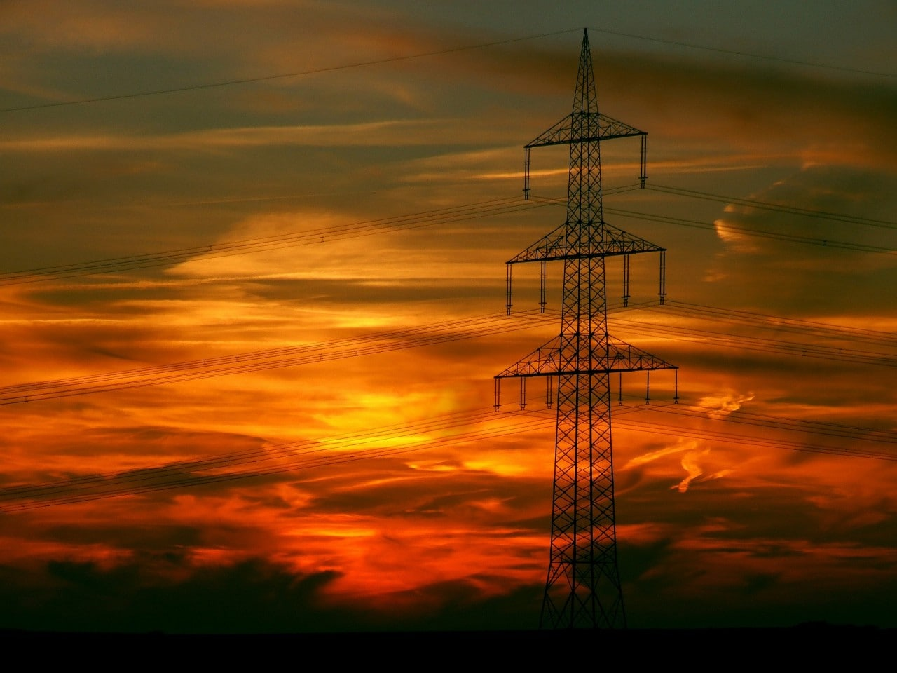 Power poles seen at sunset, representing the energy market.