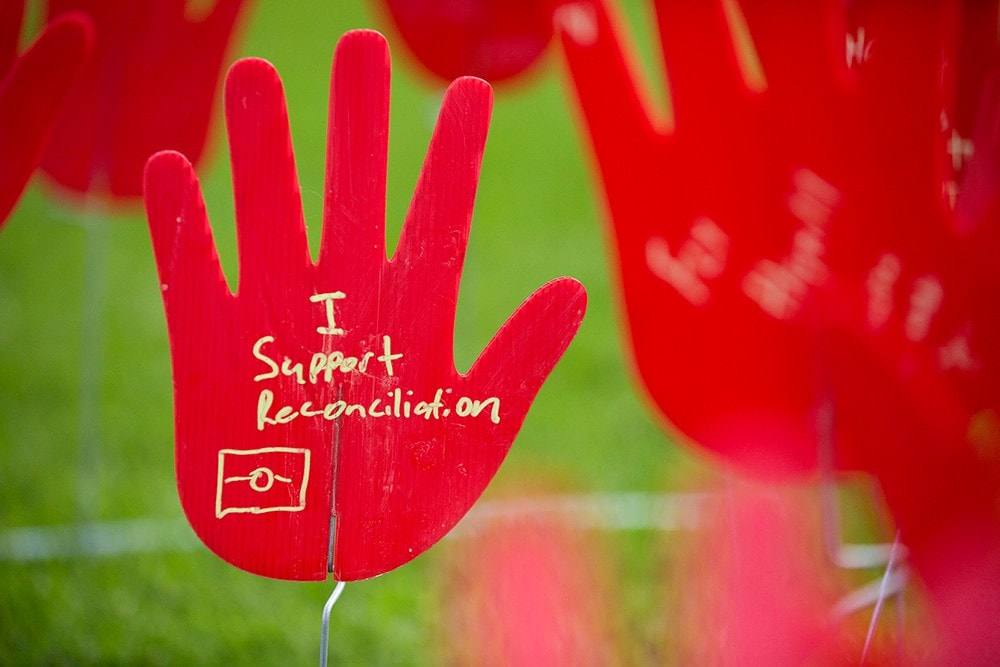 A plastic hand with 'I support Reconciliation' written on it