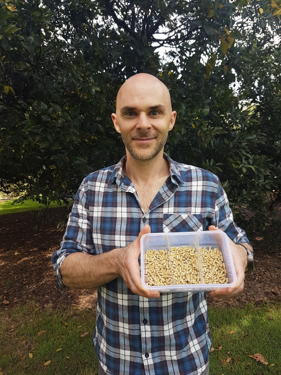 A photo of researcher Sean Coogan in Hyde Park Sydney, with container of ibis feed.