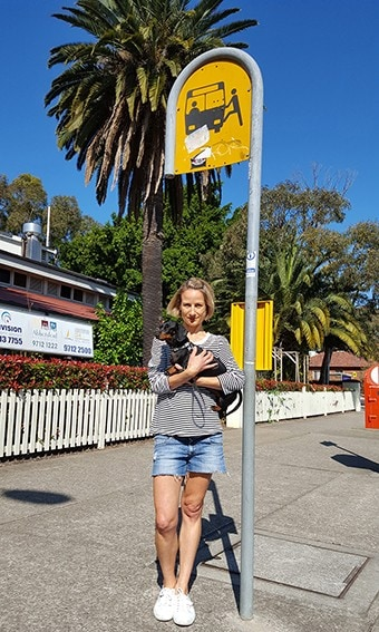 Dr Jennifer Kent with her dog Olive standing at the bus stop.