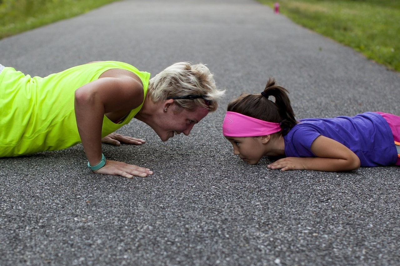 Older lady with girl doing push ups outside